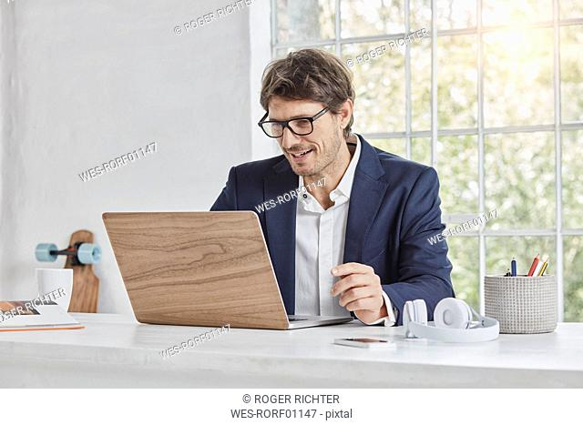 Smiling businessman using laptop on desk