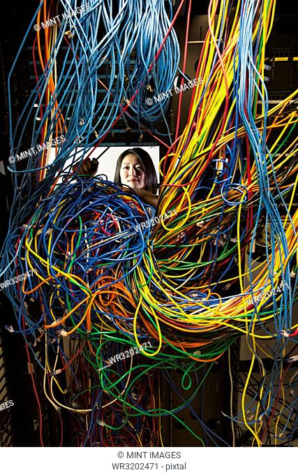 Asian female technician working on a tangled mess of CAT 5 cables in a server room