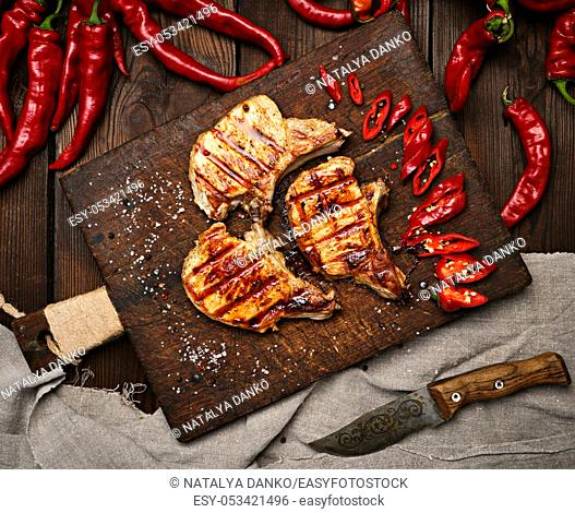 pork fried steak on the rib lies on a vintage brown wooden board, next to fresh red chili peppers, top view