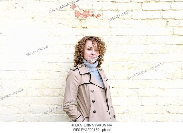 Portrait of smiling woman with curly hair wearing beige trenchcoat