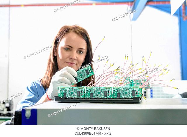 Female worker inspecting circuit boards in circuit board assembly factory
