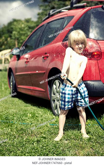 Boy holding water hose in backyard