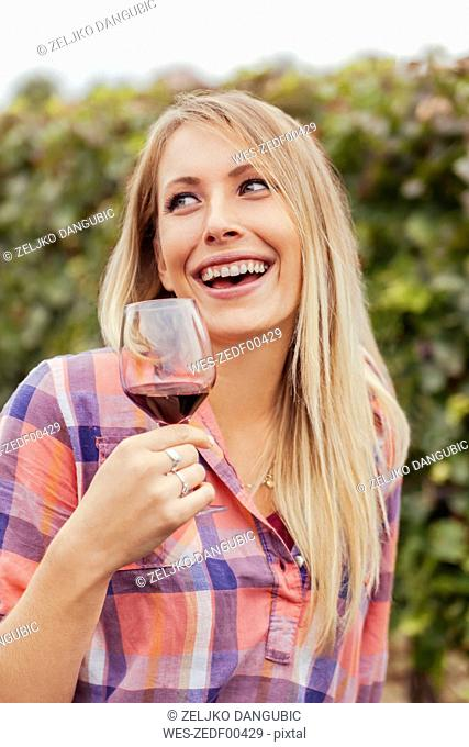 Happy young woman in a vineyard holding glass of red wine