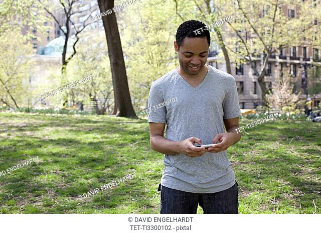 Man in casual clothing texting in park