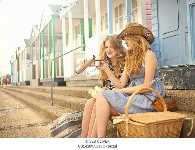 Teenage girls sitting on steps in front of beach hut, drinking flask of tea