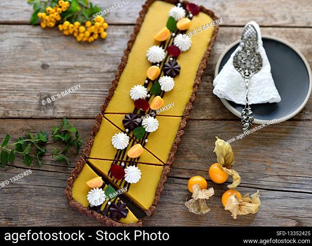 Vegan pumpkin chocolate tart with cream dots and fresh physalis