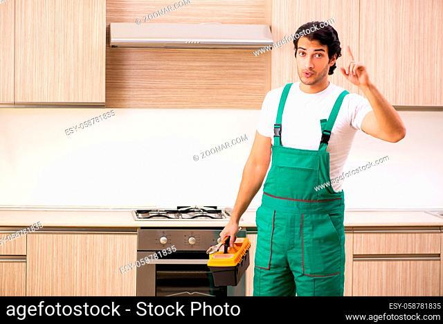 Young contractor repairing oven in kitchen