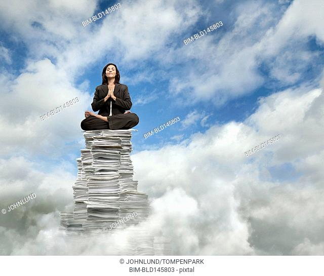 Mixed race businesswoman sitting in clouds on stack of paper