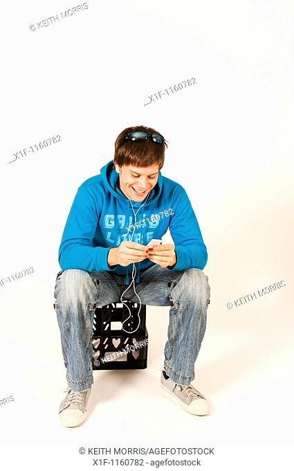 Young man listening to music on his iPod sitting on a plastic crate, UK