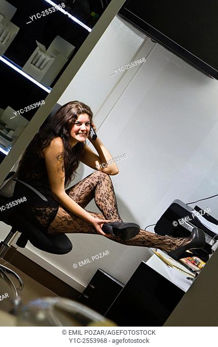 Sexy secretary laughing and legs on desk