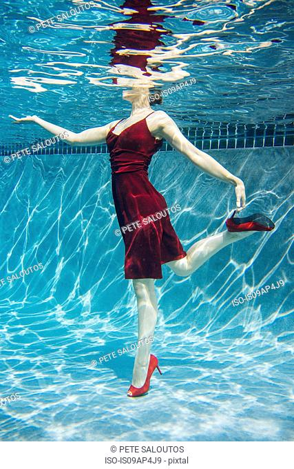 Mature woman wearing red dress and high heels, standing on one leg, underwater view