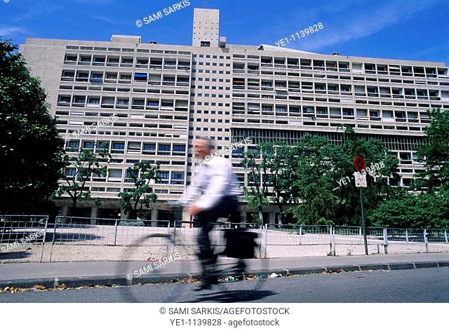 Cyclist passing the Cite Radieuse, a modernist residential housing complex designed by Le Corbusier, in Marseille, France