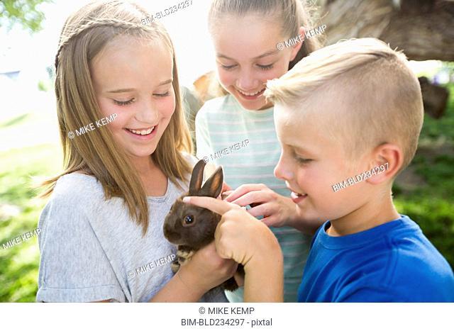 Caucasian boy and girls petting rabbit