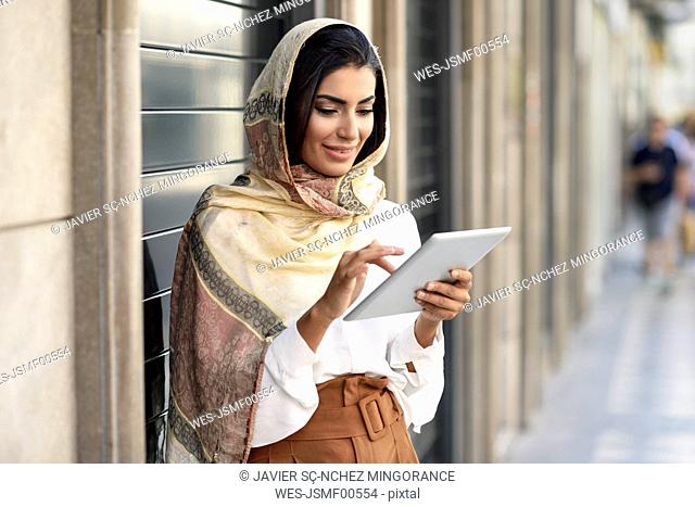 Spain, Granada, young muslim woman wearing hijab using tablet outdoor
