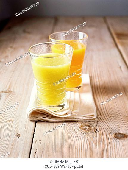 Glasses of fresh apple and orange juice on folded napkin