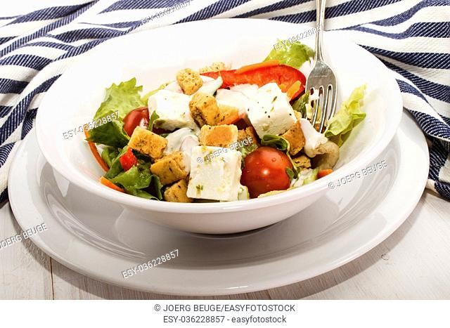 fresh salad with tomato, croutons, slice red bell pepper and goat cheese