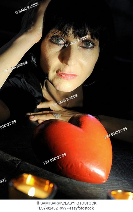 Mature woman looking pensive with a heart shape - looking for love concept