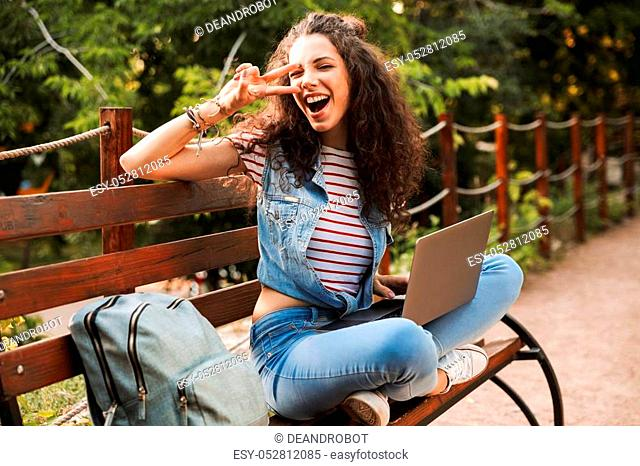 Photo of happy funny woman 20s with curly hair gesturing peace sign while sitting on bench in green park and studying or working on silver laptop