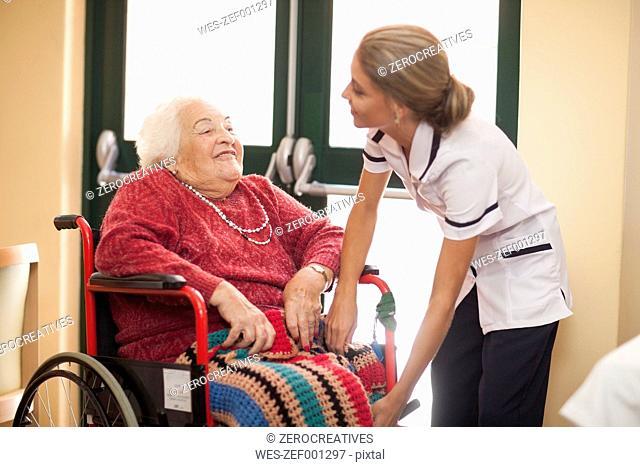 Nurse caring for senior woman in wheelchair