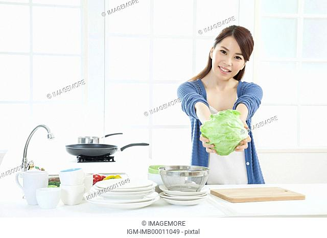 Young woman holding cabbage and smiling at the camera