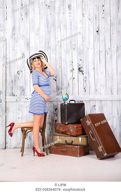 Stylish pregnant lady tourist with suitcases near wooden wall