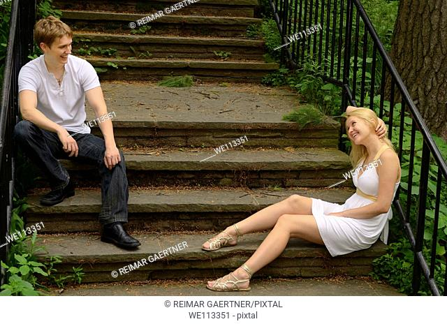 Smiling couple looking at each other while sitting on stone stairs in a park
