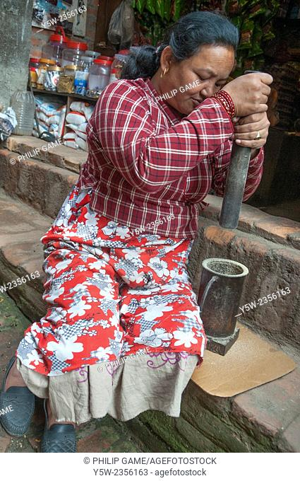 Woman pounding grain at Bhaktapur, Kathmandu Valley, Nepal