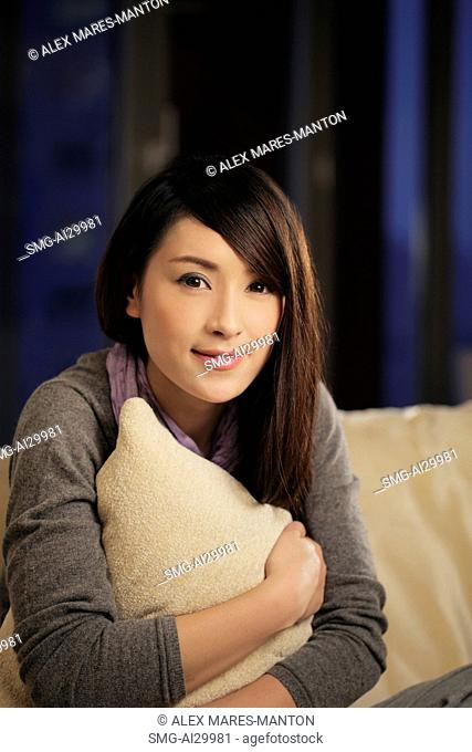 Young woman holding a pillow and smiling