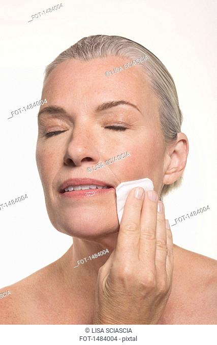 Close-up of mature woman with eyes closed wiping face against white background