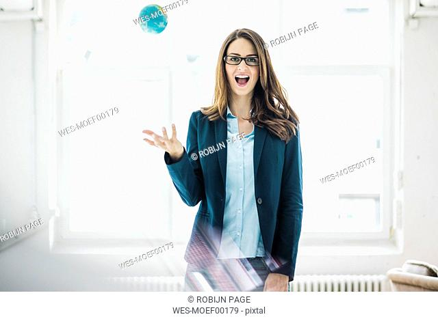Portrait of businesswoman throwing small globe in the air