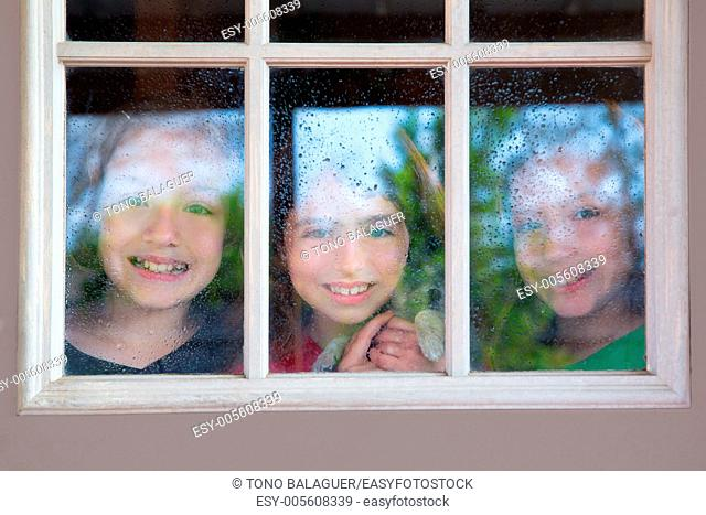three sister friends looking through the window with a pup and raindrops