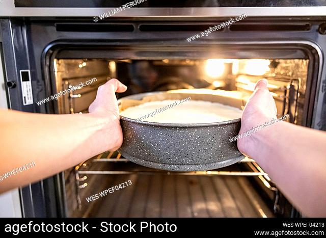 Woman putting a cheesecake in the oven