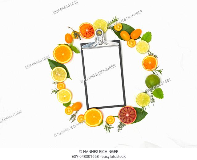 a lot of different fresh citrus fruits on white crumpled paper background