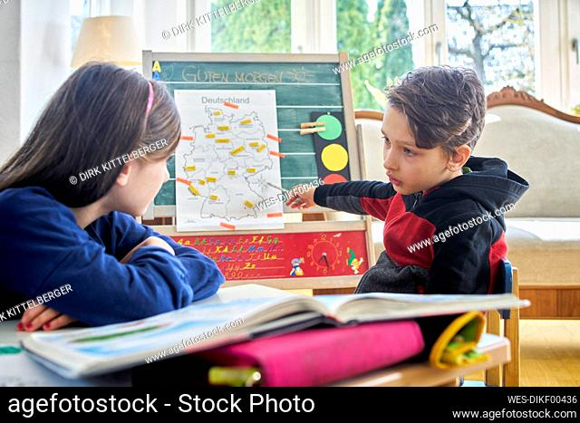 Brother and sister learing at home during school closure