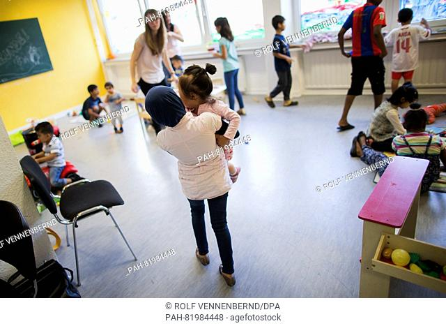 Fatima from Syria carrying a child at a day care centre for refugees in Essen, Germany, 12 July 2016. PHOTO: ROLF VENNENBERND/DPA | usage worldwide