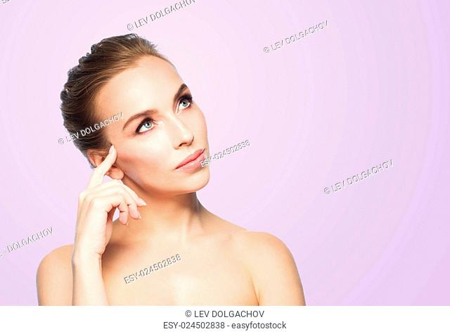 beauty, people and health concept - beautiful young woman touching her face over violet background