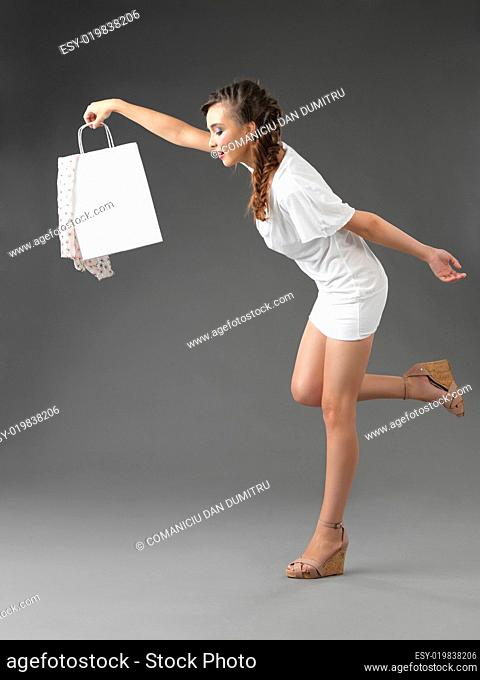 fashionable young woman holding shoppping bag, tumbling