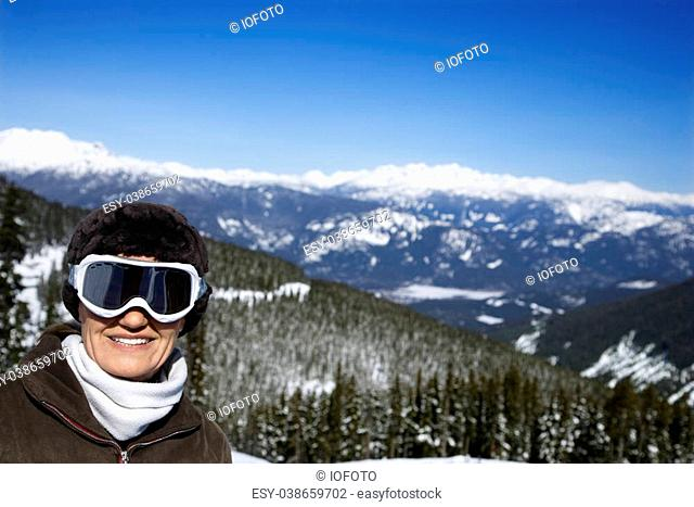 Caucasian middle-aged woman skier posing on mountain
