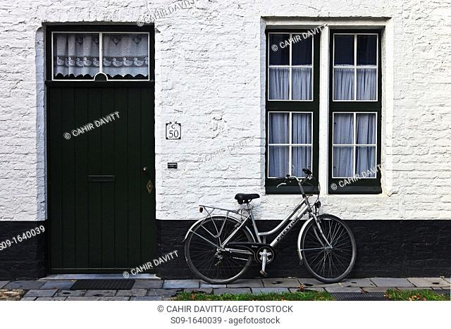 Traditional architectural door and window detail of a Beguinage, with a bike in Brugge Sint Michiels, Brugge Bruges, Belgium