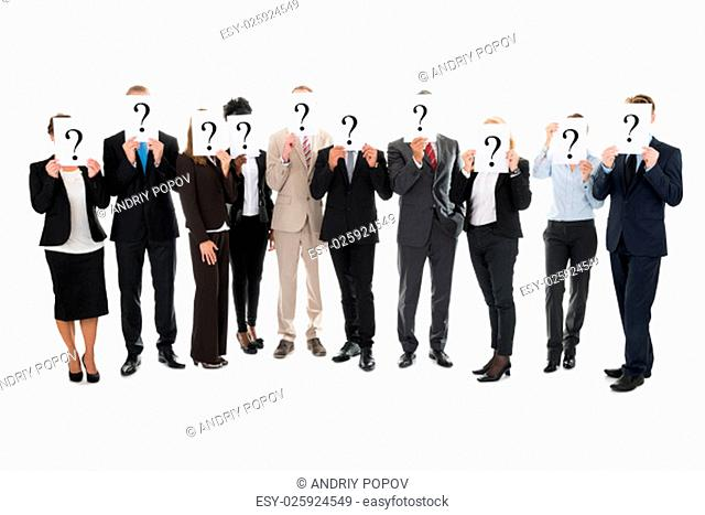 Full length of business team hiding faces with question mark signs against white background