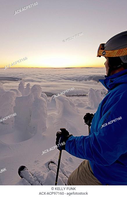 A skier among snow ghosts surveys the beautiful landscape before sunrise at the top of Sun Peaks Resort, Thompson Okangan region, British Columbia, Canada