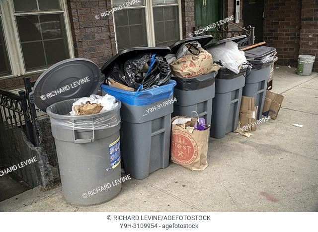 Overflowing trash cans, awaiting pick up, outside of an apartment building in the Greenpoint neighborhood of Brooklyn in New York on Sunday, June 3, 2018