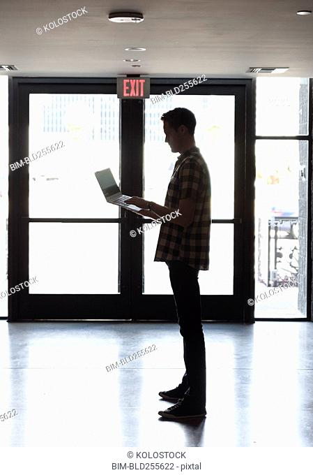 Caucasian man standing near doorway using laptop