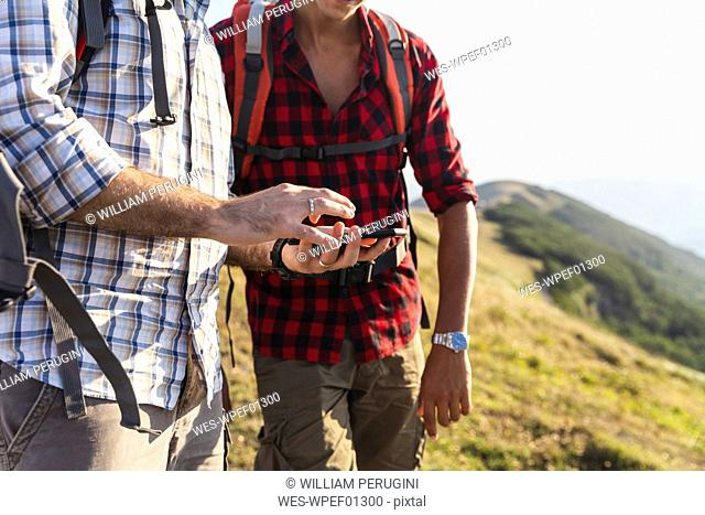 Italy, Monte Nerone, close-up of two men hiking and using smartphone in mountains