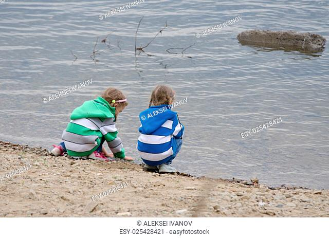 Two children enthusiastically walk along the river bank