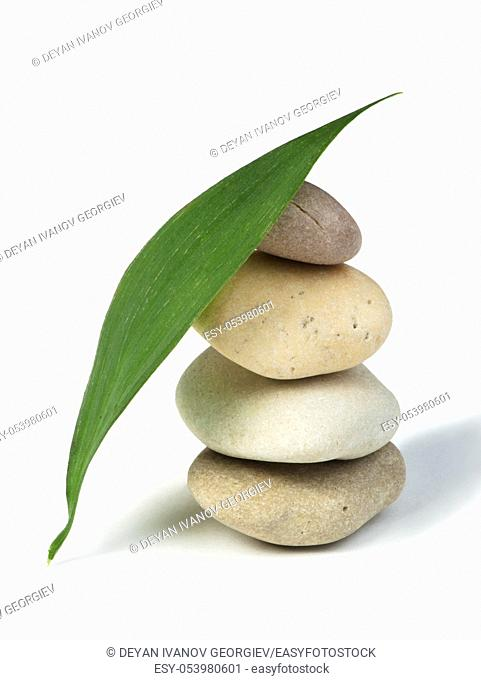 Stacked stones and green leafs on white background