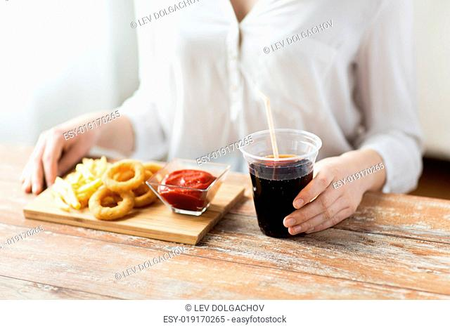fast food, people and unhealthy eating concept - close up of woman eating deep-fried squid rings, french fries with ketchup and drinking cola on wooden table