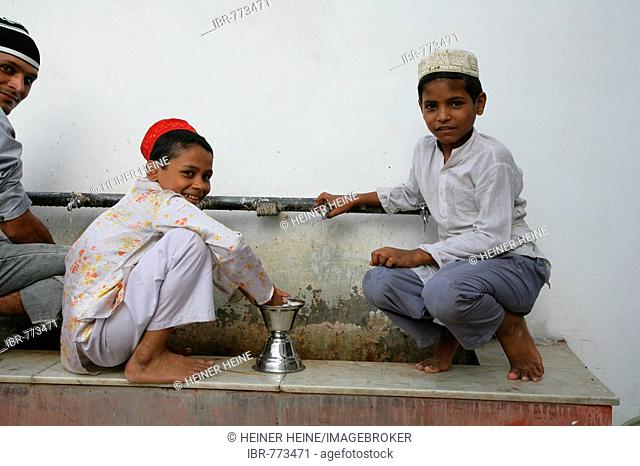 Boys cleaning ritual objects used at a shrine, Bareilly, Uttar Pradesh, India, Asia