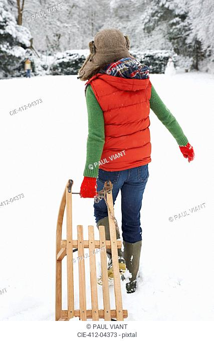 Woman pulling wooden sled in snow