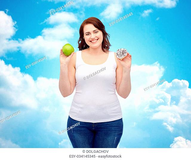 healthy eating, junk food, diet and choice people concept - smiling plus size woman choosing between apple and cookie over blue sky and clouds background